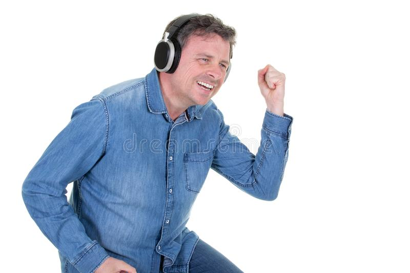 Handsome man wearing  blue shirt is standing with a cheerful smile and dancing with his eyes closed over the white background stock image