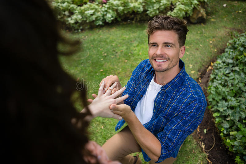 Handsome man wearing engagement ring to woman stock photo