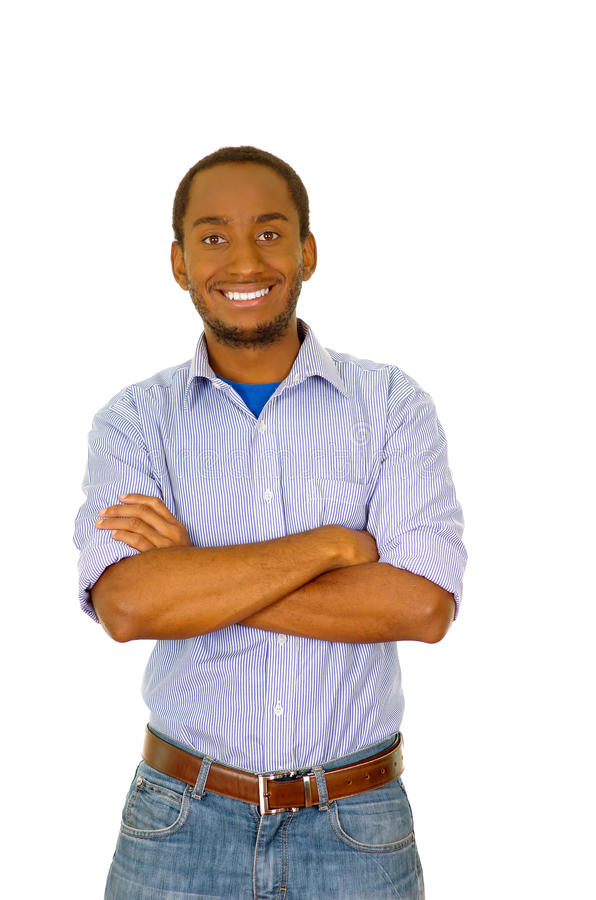 Handsome man wearing jeans and light blue shirt standing in front of camera smiling with arms crossed, white studio stock image