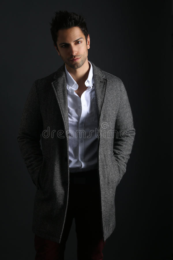 Handsome man wearing a long coat stock photos
