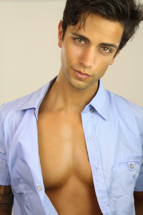 Handsome man wearing an open shirt. Portrait of a handsome male wearing a blue shirt stock photography