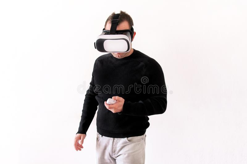 Handsome man wearing and playing virtual reality on isolated white background. Boy action in virtual reality helmet. VR glasses. VR Box, VR headset. Young royalty free stock images