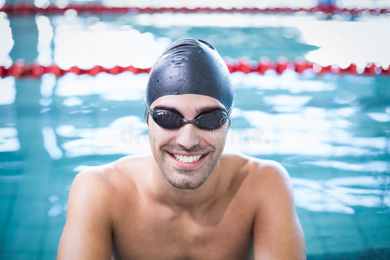 Handsome man wearing swim cap and goggles. At the pool stock photo