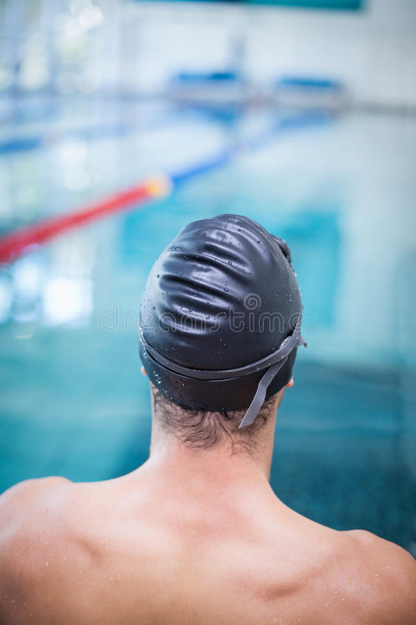 Handsome man wearing swim cap and goggles. At the pool royalty free stock images