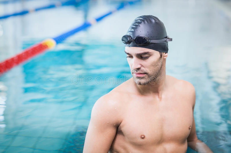 Handsome man wearing swim cap and goggles. At the pool stock images