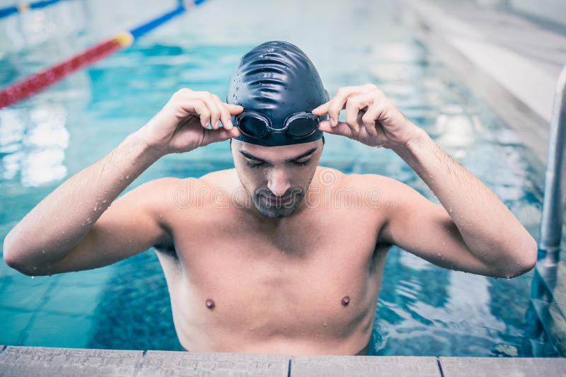Handsome man wearing swim cap and goggles. At the pool royalty free stock photo