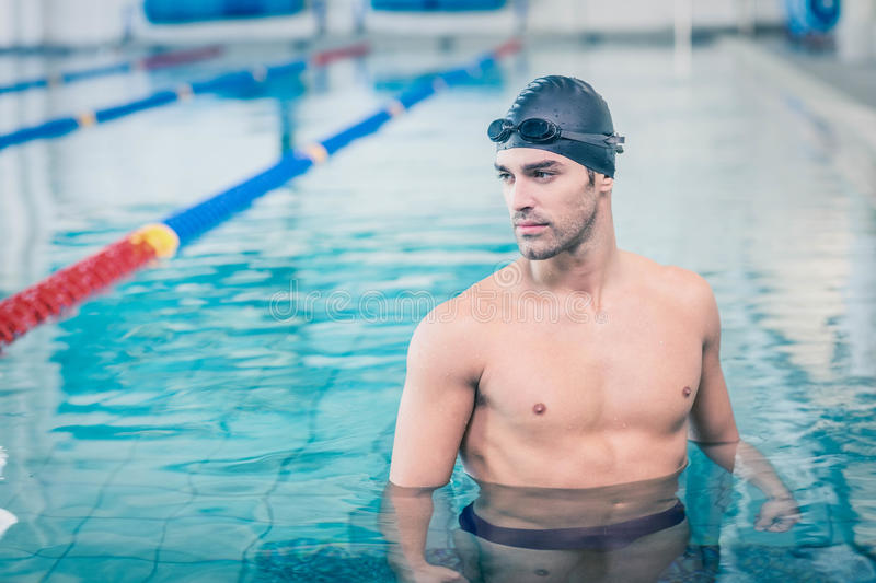 Handsome man wearing swim cap and goggles. At the pool stock photography