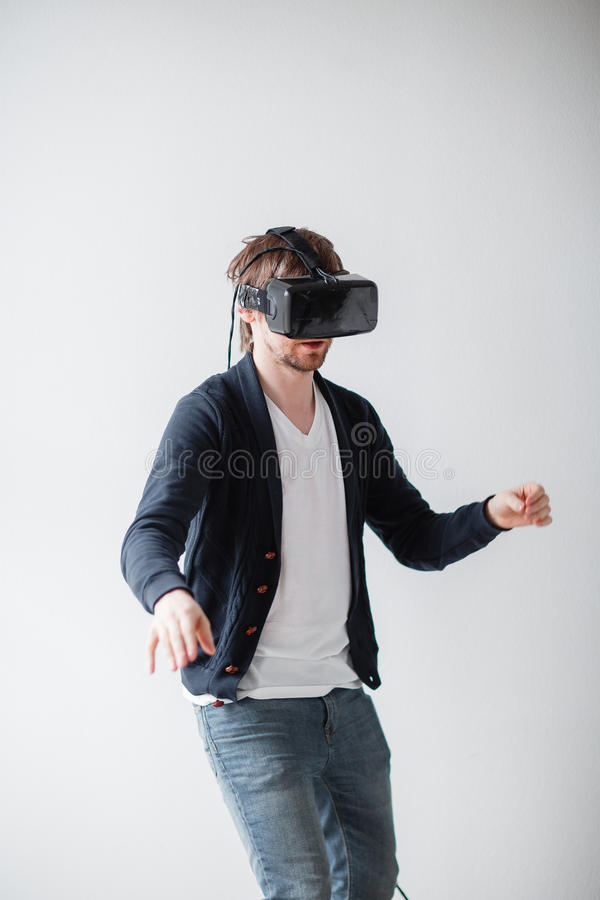 Handsome man wearing virtual reality glasses isolated on a gray background stock photos