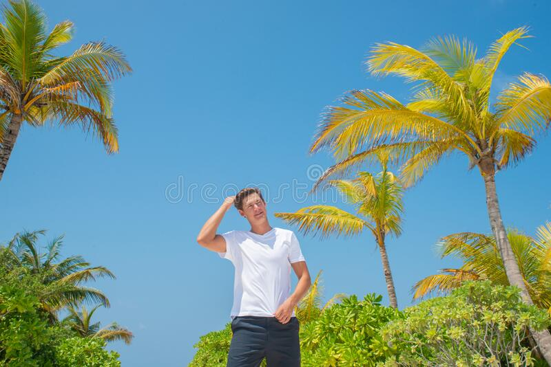 Handsome man wearing white t-shirt and black shorts standing at tropical sandy beach at island luxury resort royalty free stock photography