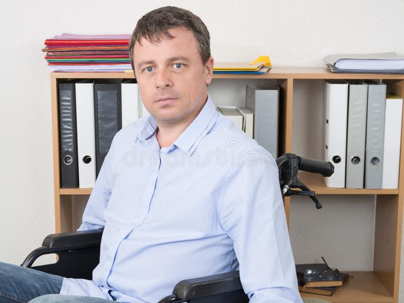 handsome man in wheelchair at home office royalty free stock photo