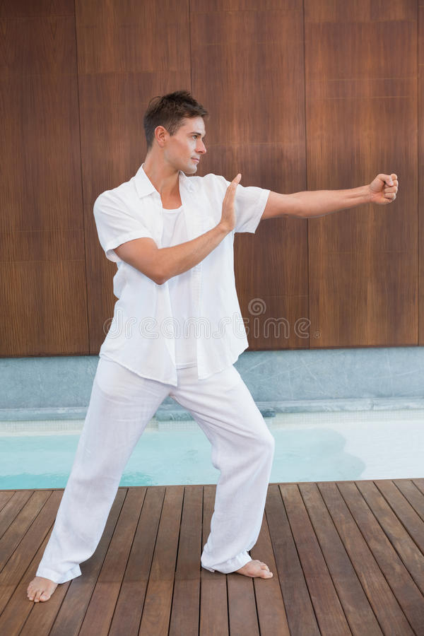 Handsome man in white doing tai chi. In health spa royalty free stock photography