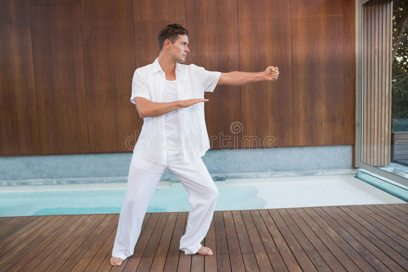 Handsome man in white doing tai chi. In health spa stock image