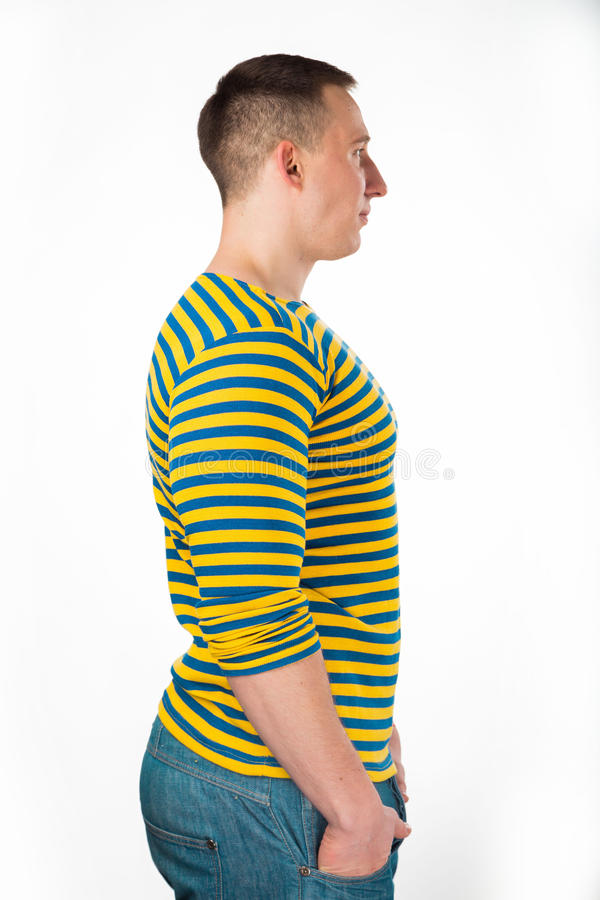 Handsome man on white. Muscular man in a striped vest, in casual clothes posing on light background. strength, fitness, fashion, health, muscles. Young strong stock image