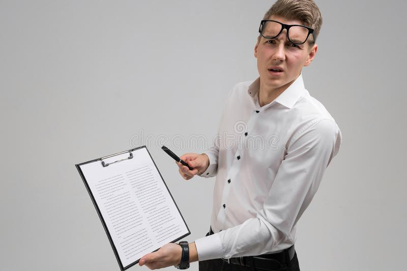 Young man with glasses and insurance questionnaire in hand isolated on white background stock photos