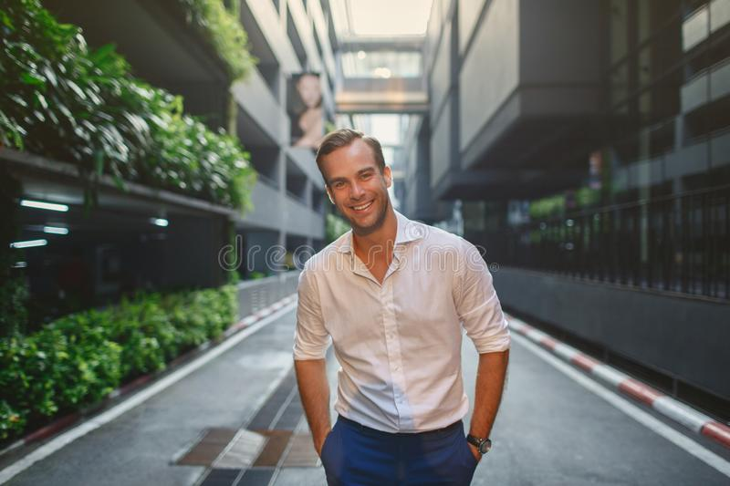 Handsome man in white shirt smiling standing near the mall royalty free stock photography