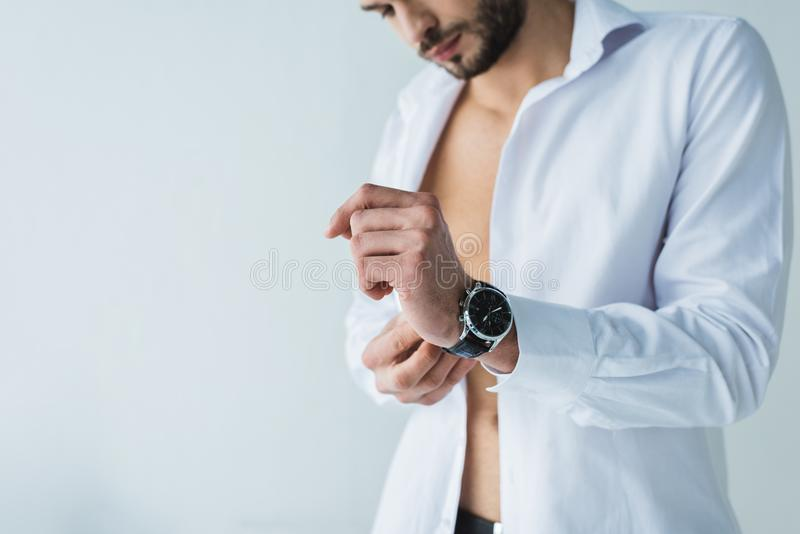 handsome man in white shirt wearing wristwatch, stock photography