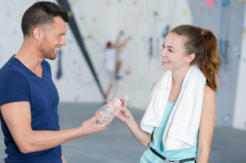 Handsome man and woman drink water in gym royalty free stock photography