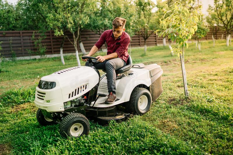 Handsome man, worker using grass cutting equipment for landscaping works stock photos