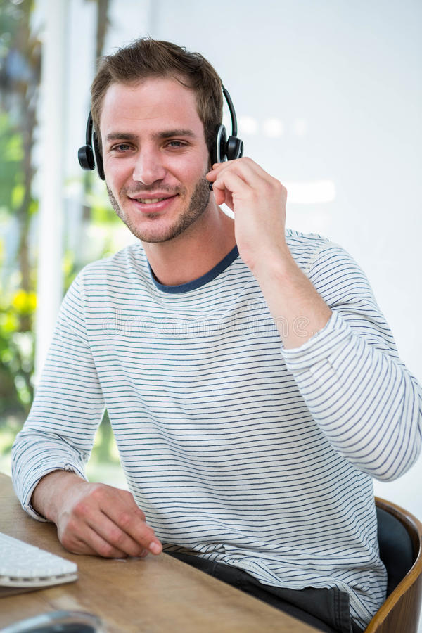 Handsome man working with headset. In a bright office stock images