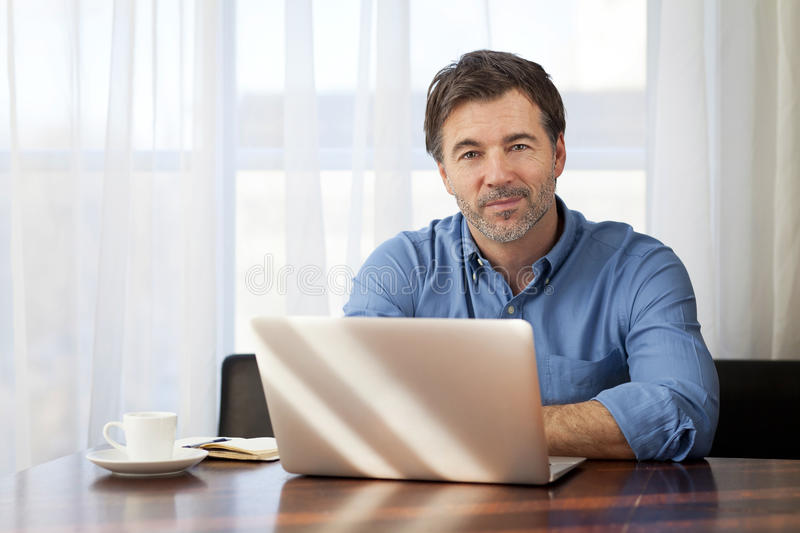 Handsome Man working At Home On His Laptop stock photo