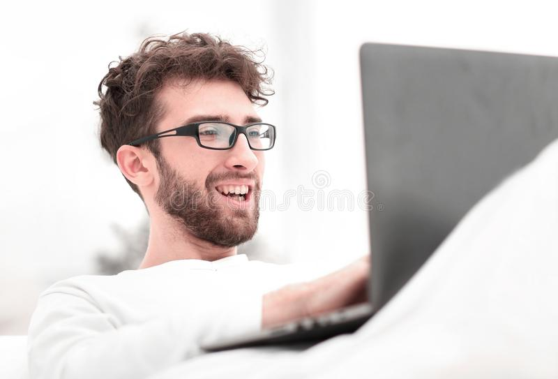 Handsome man working on laptop lying on bed stock photos