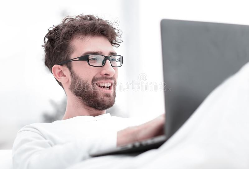 Handsome man working on laptop lying on bed. Closeup.handsome man working on laptop lying on bed stock image