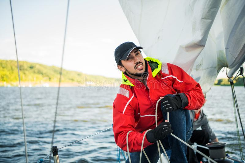 Handsome man on yacht touches white sail called assymetric spinnaker, works with tackle in sea at summer day, under view. Handsome man on yacht touches white royalty free stock images