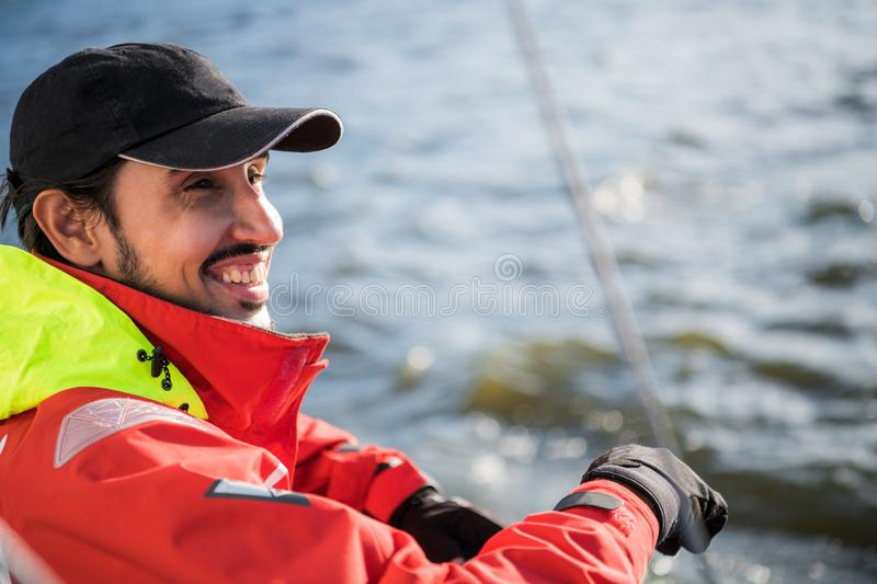 Handsome man on yacht touches white sail called assymetric spinnaker, works with tackle in sea at summer day, under view. Handsome man on yacht touches white stock photo
