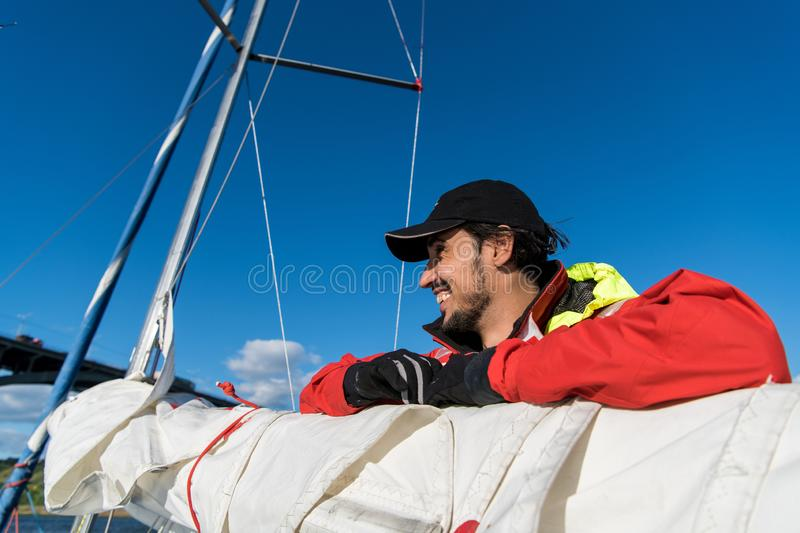 Handsome man on yacht touches white sail called assymetric spinnaker, works with tackle in sea at summer day, under view. Handsome man on yacht touches white stock images