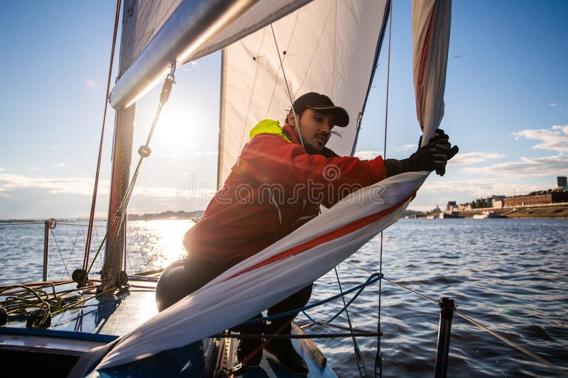 Handsome man on yacht touches white sail called assymetric spinnaker, works with tackle in sea at summer day, under view. Handsome man on yacht touches white royalty free stock photos