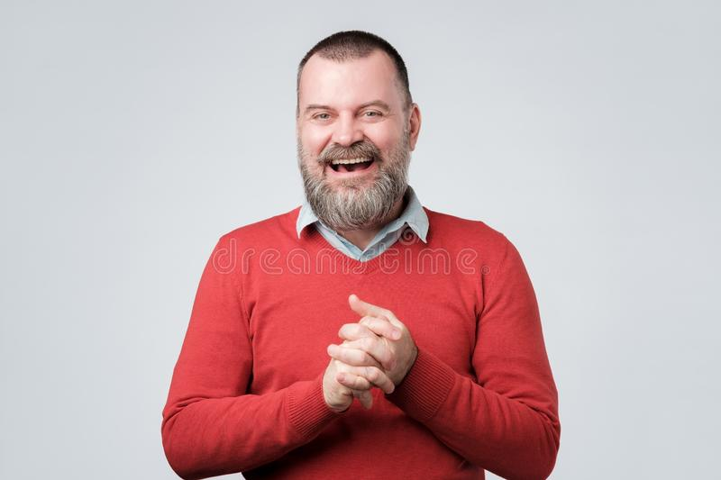 Handsome mature bearded man in red sweater laughing stock photo