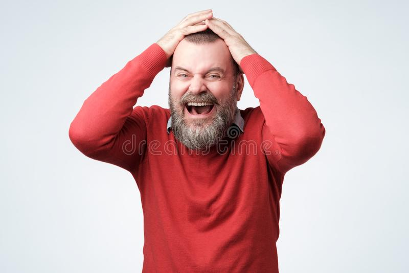 Handsome mature bearded man in red sweater laughing stock images