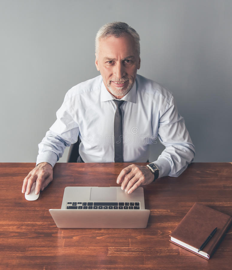 Handsome mature businessman. In formal suit is looking at camera and smiling while working with a laptop in office royalty free stock images