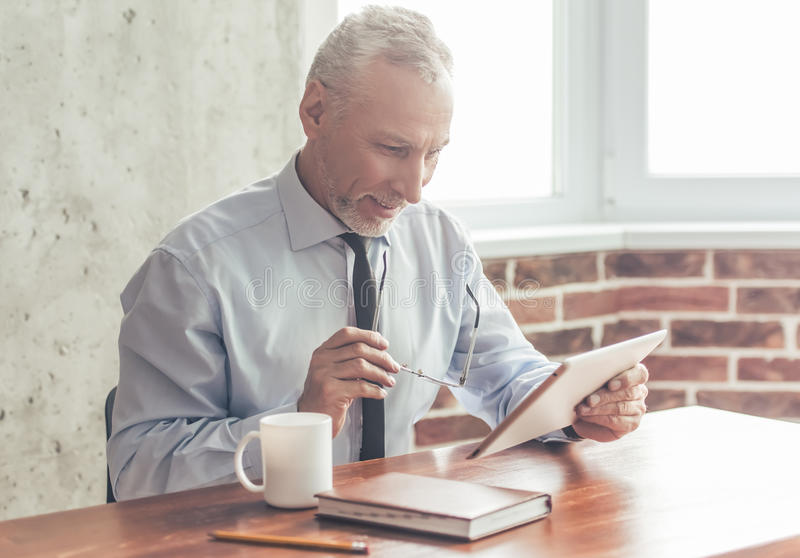 Handsome mature businessman. In formal suit is using a digital tablet, holding glasses and smiling while working in office royalty free stock photography