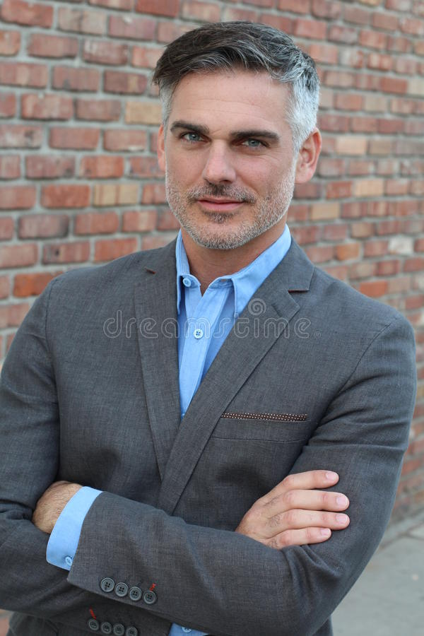 Handsome mature businessman smiling crossing his arms royalty free stock photos