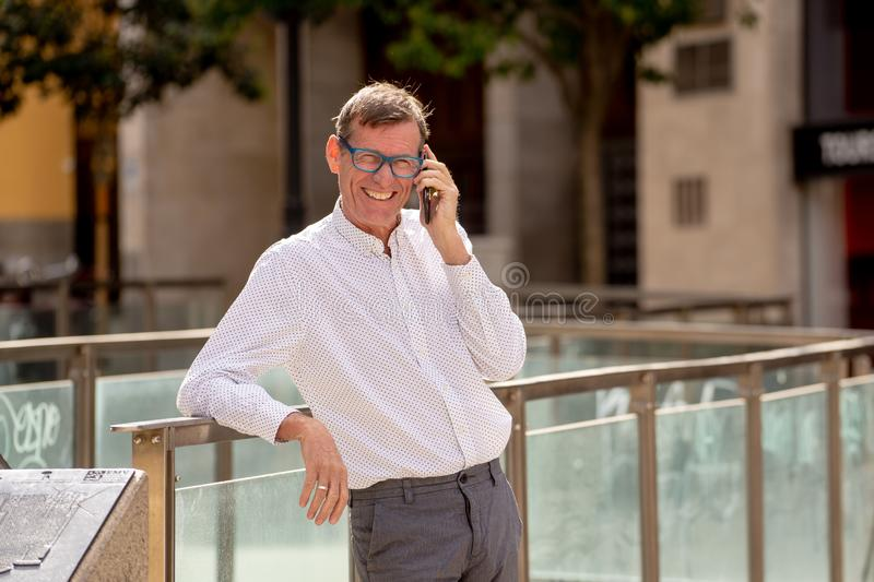 Handsome mature creative freelance businessman talking on the mobile phone and smiling while walking outdoor urban area in the stock images