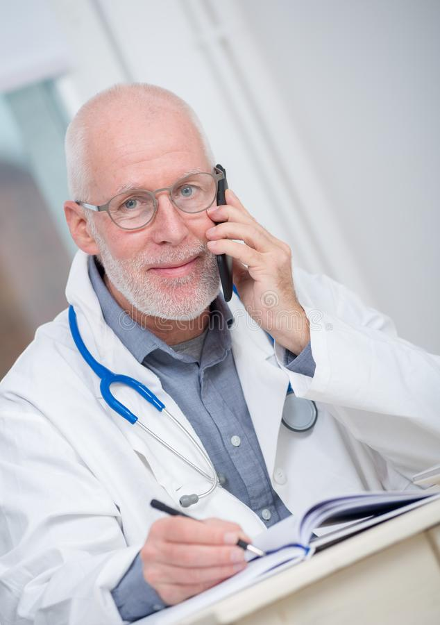 Mature doctor on phone at his office royalty free stock photography
