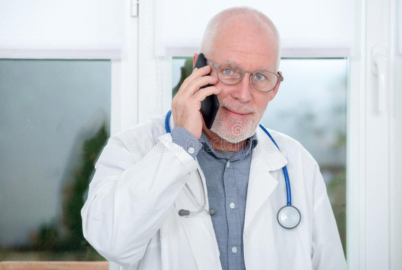 Mature doctor on phone in his office royalty free stock photos