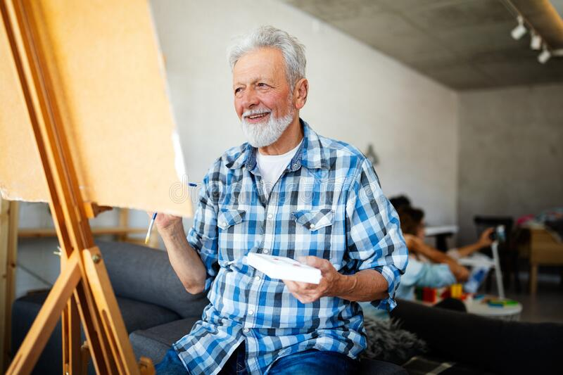 Handsome mature man artist paints on canvas painting on the easel. Handsome senior man artist paints on canvas painting on the easel royalty free stock photography