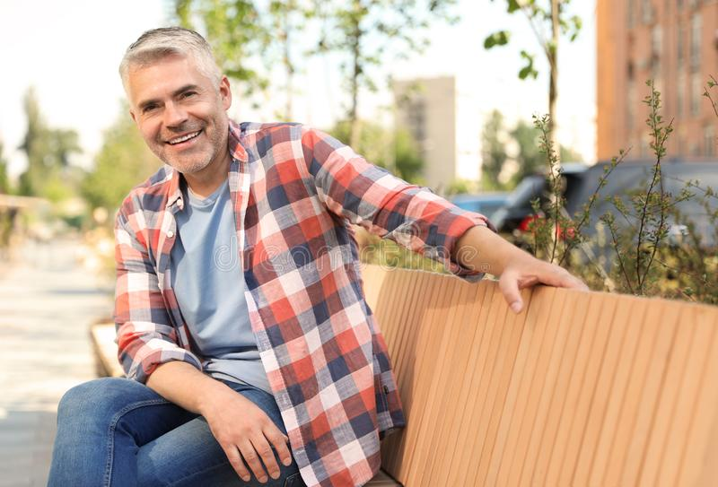 Handsome mature man on bench stock photography