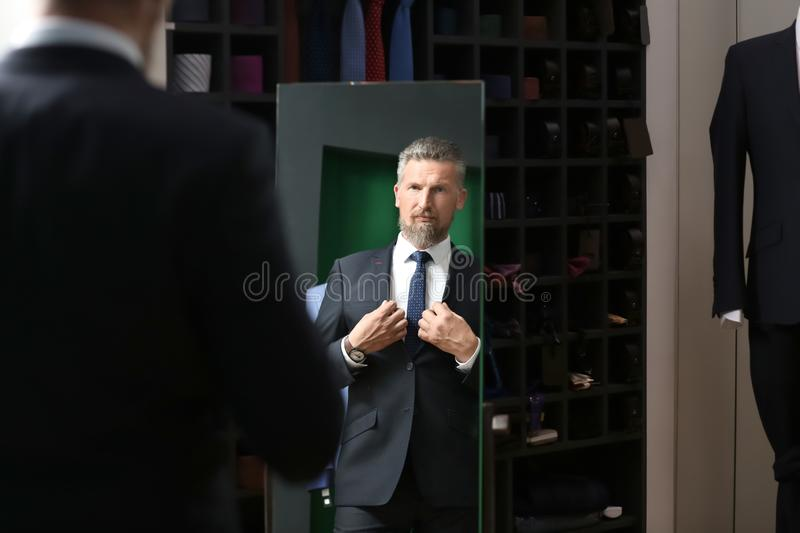 Handsome mature man looking into mirror while trying on new suit at store royalty free stock photography