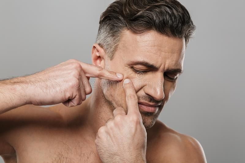 Handsome mature man naked take care of his skin squeezes out a pimple. Image of handsome mature man standing isolated over grey wall background naked take care royalty free stock images