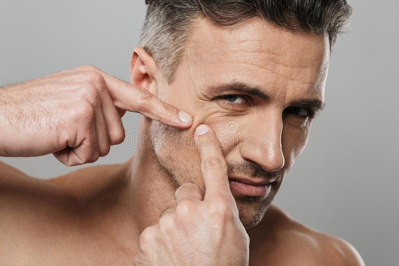 Handsome mature man naked take care of his skin squeezes out a pimple. Image of handsome mature man standing isolated over grey wall background naked take care stock photos