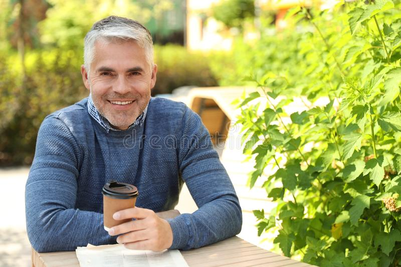 Handsome mature man sitting at table. Space for text stock photos