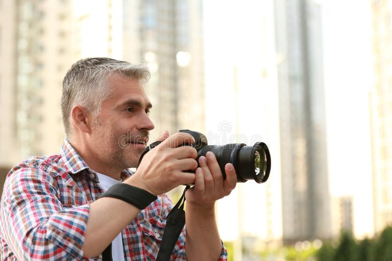 Handsome mature man taking photo with professional camera outdoors. Space for text stock image