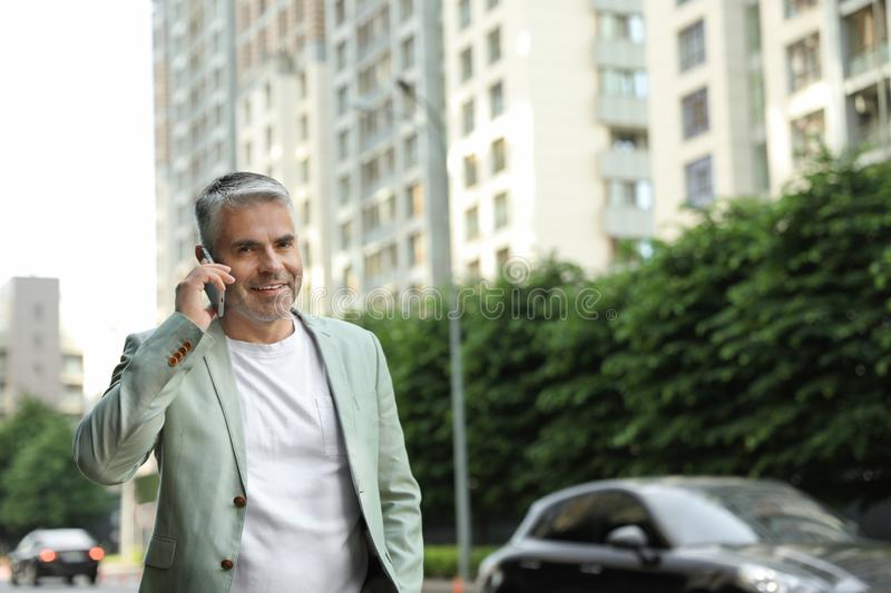 Handsome mature man talking on phone in city center royalty free stock images