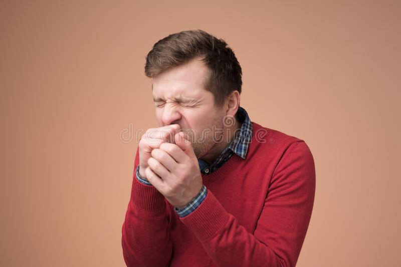 Handsome mature manin red sweater coughing a lot royalty free stock photo