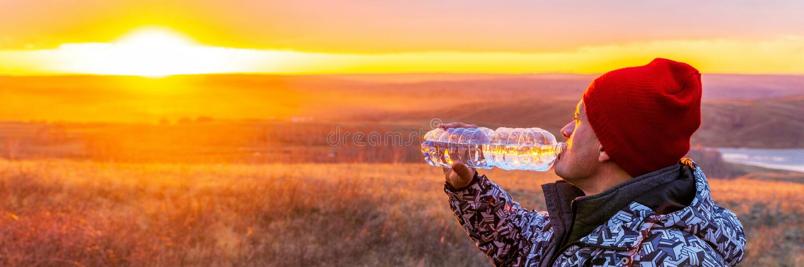 Handsome mature men drink clean spring water from a plastic bottle. Handsome mature man drink clean spring water from a plastic bottle on the background of the royalty free stock photo