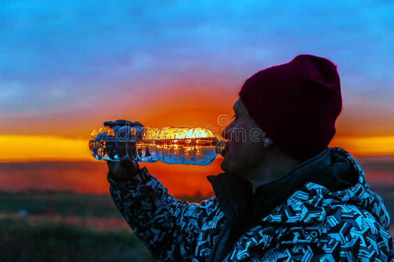 Handsome mature men drink clean spring water from a plastic bottle. Handsome mature man drink clean spring water from a plastic bottle on the background of the royalty free stock images