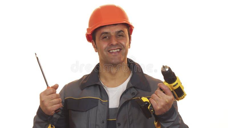 Mature repairman choosing between screwdriver and drilling machine stock image